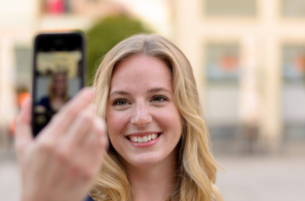 Smiling young woman taking her selfie on her mobile phone outdoors in an urban street with focus to her face as she poses for the camera